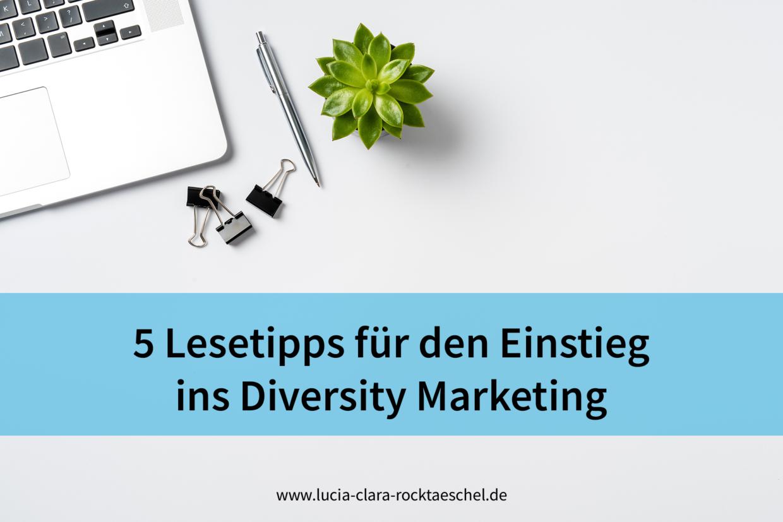 """Text """"5 Lesetipps für den Einstieg ins Diversity Marketing"""" auf hellblauer Bauchbinde. Hintergrundbild: weißer Hintergrund mit Laptop, Stift und kleiner Grünpflanze von oben fotografiert."""