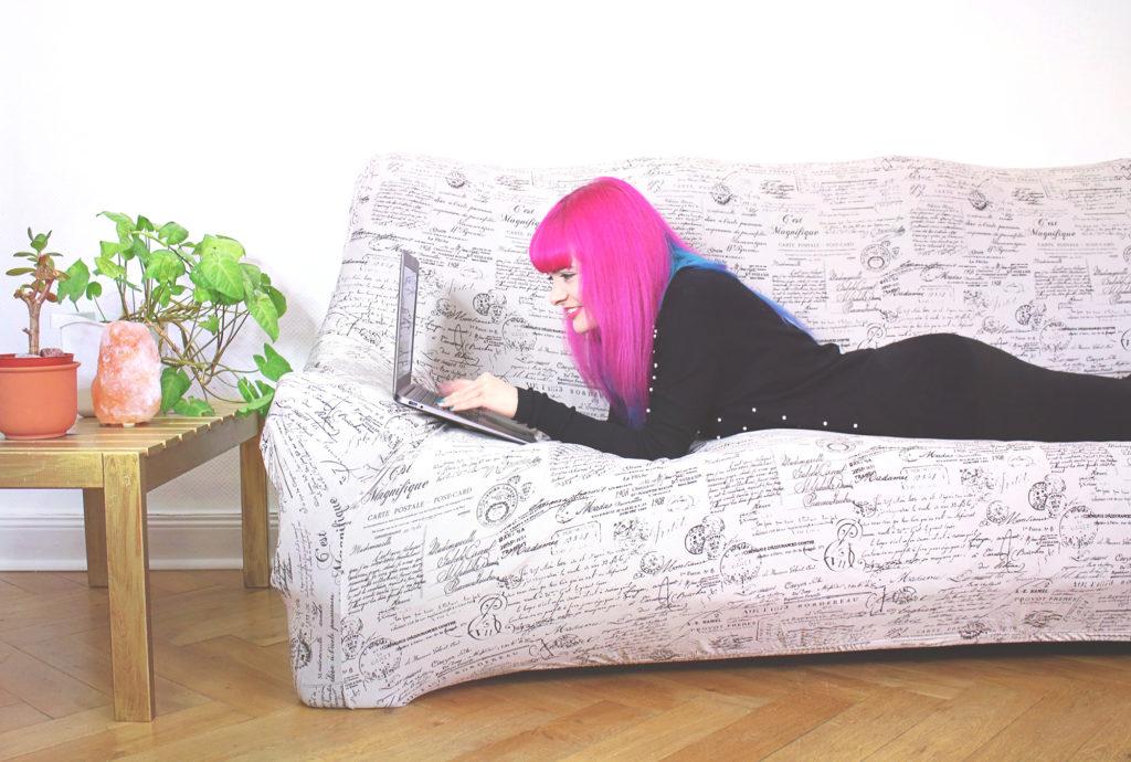 Lucia Clara Rocktäschel liegt auf dem Sofa in ihrem Büro und arbeitet am Laptop.