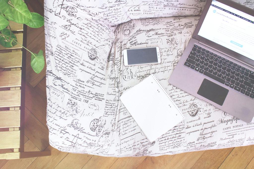 Laptop, Smartphone und Schreibheft liegen auf einem Sofa. Von oben fotografiert.
