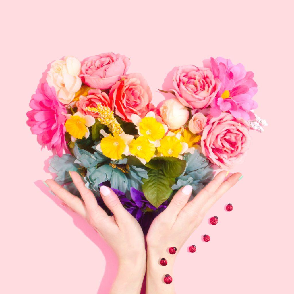 Herz aus Blumen in Regenbogenfarben