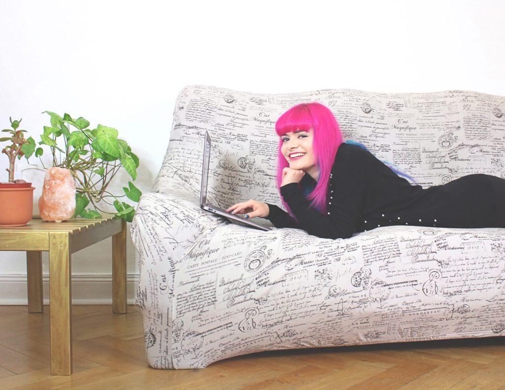 Lucia liegt mit Laptop auf dem Sofa und lächelt in die Kamera
