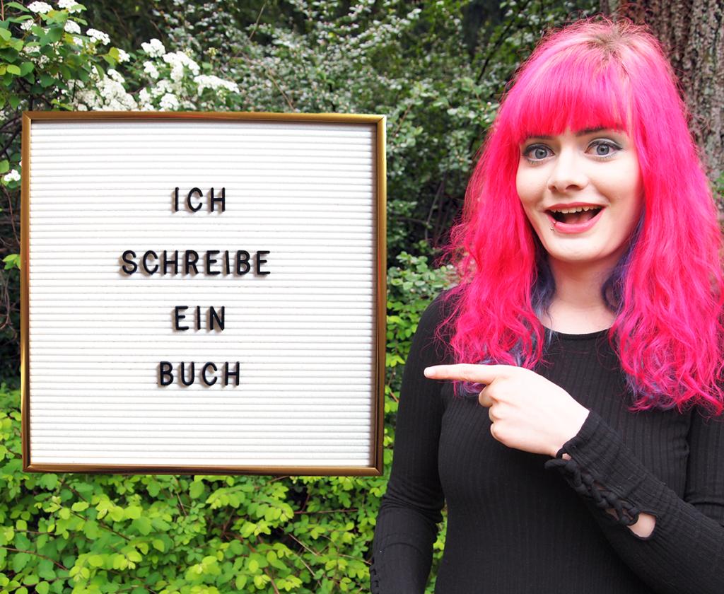 Lucia steht draußen im Grünen und zeigt auf ein ins Bild gephotoshopptes Letterboard mit der Aufschrift: Ich schreibe ein Buch.