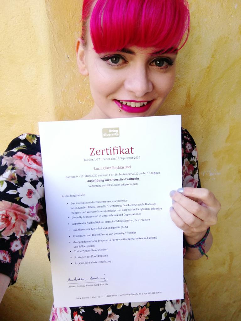 Lucia hält ihr Zertifikat der Ausbildung zur Diversity-Trainerin in der Hand und lächelt in die Kamera.