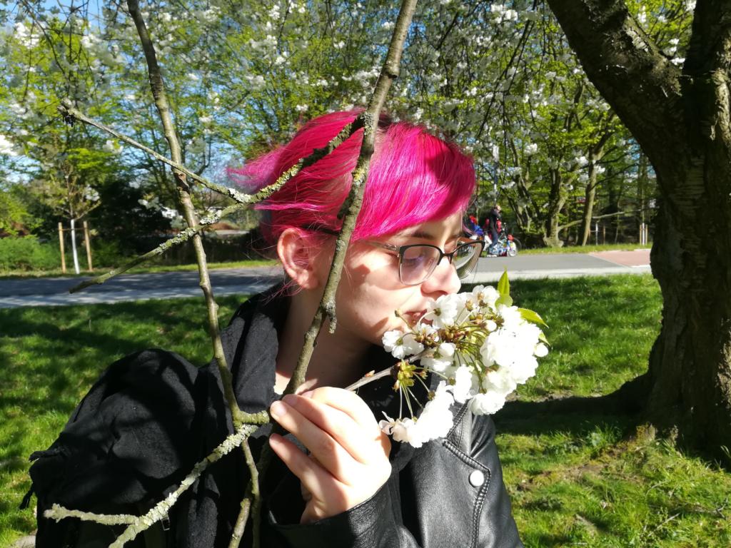 Lucia steht im Grünen und riecht an der weißen Blüte eines Baumes.