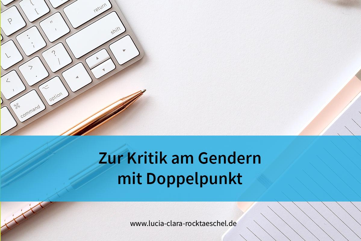 """Titel des Blogbeitrags """"Zur Kritik am Gendern mit Doppelpunkt"""" auf blauer Bauchbinde. Hintergrund: Eine weiße PC-Tastatur, zwei Stifte und ein Schreibblock liegen auf einem hellrosafarbenen Untergrund."""