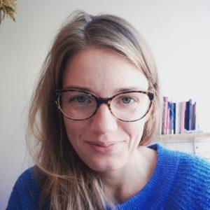 Porträt von Nora Stankewitz. Sie hat lange naturblonde Haare, trägt eine Brille und lächelt in die Kamera. Im Hintergrund ist ein Bücherregal zu sehen.