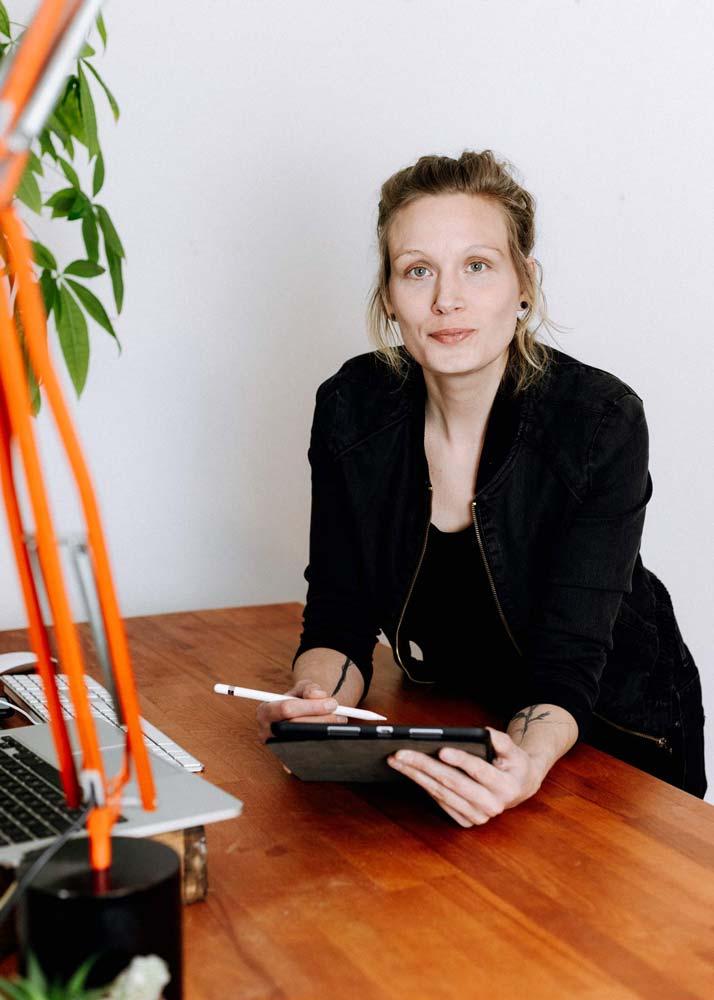 Kathrin Windhorst sitzt an einem Schreibtisch aus Holz mit Tablet und Stift in den Händen. Sie schaut herausfordernd in die Kamera.